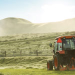 kioti tractor in a field, mowing the pasture