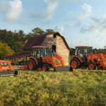 kioti tractors sold at budds all tractor llc, in a field with a barn in the background